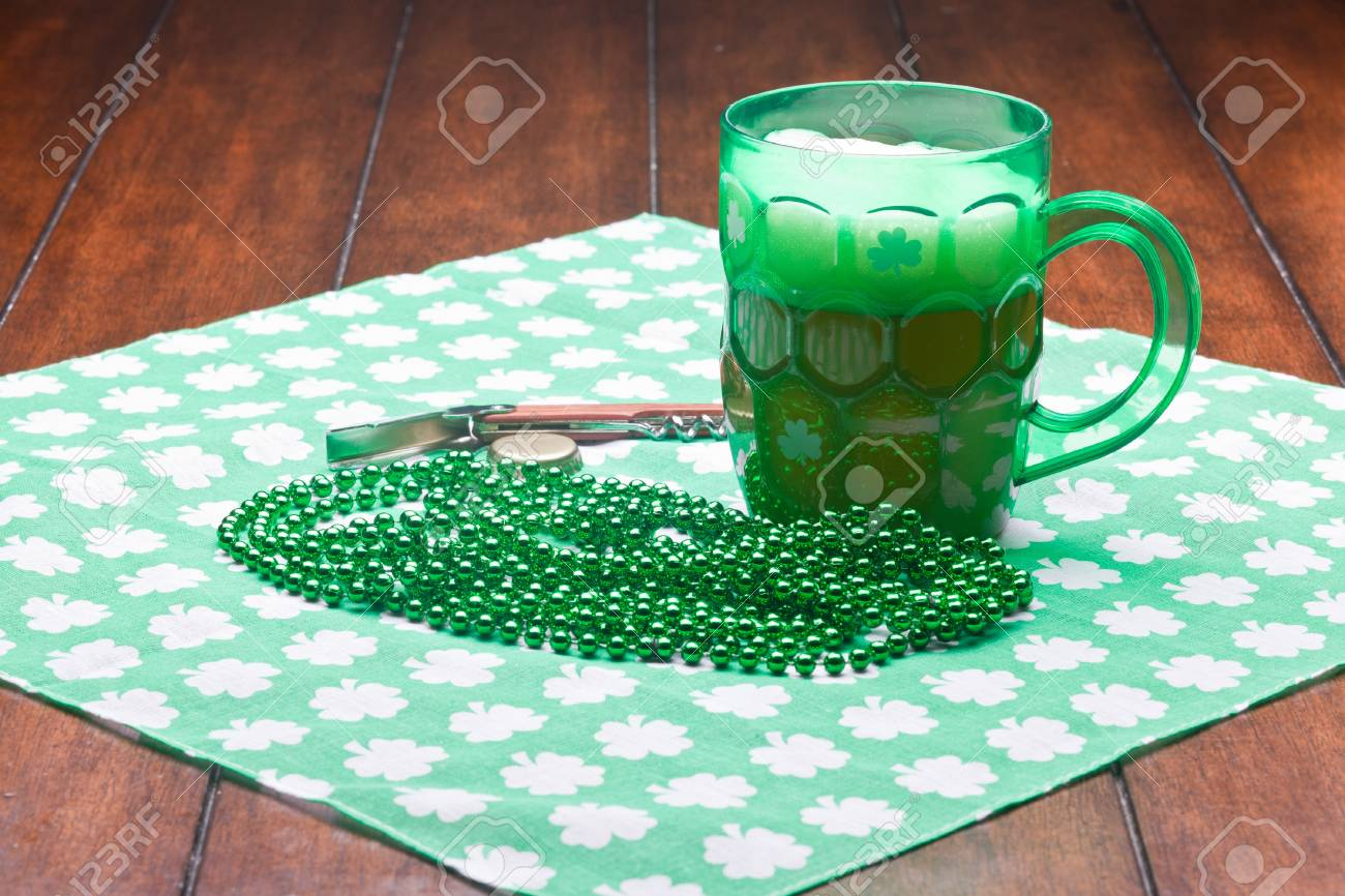 Beer mug, beads, bottle opener on a green material on wooden table. Stock Photo - 8958106