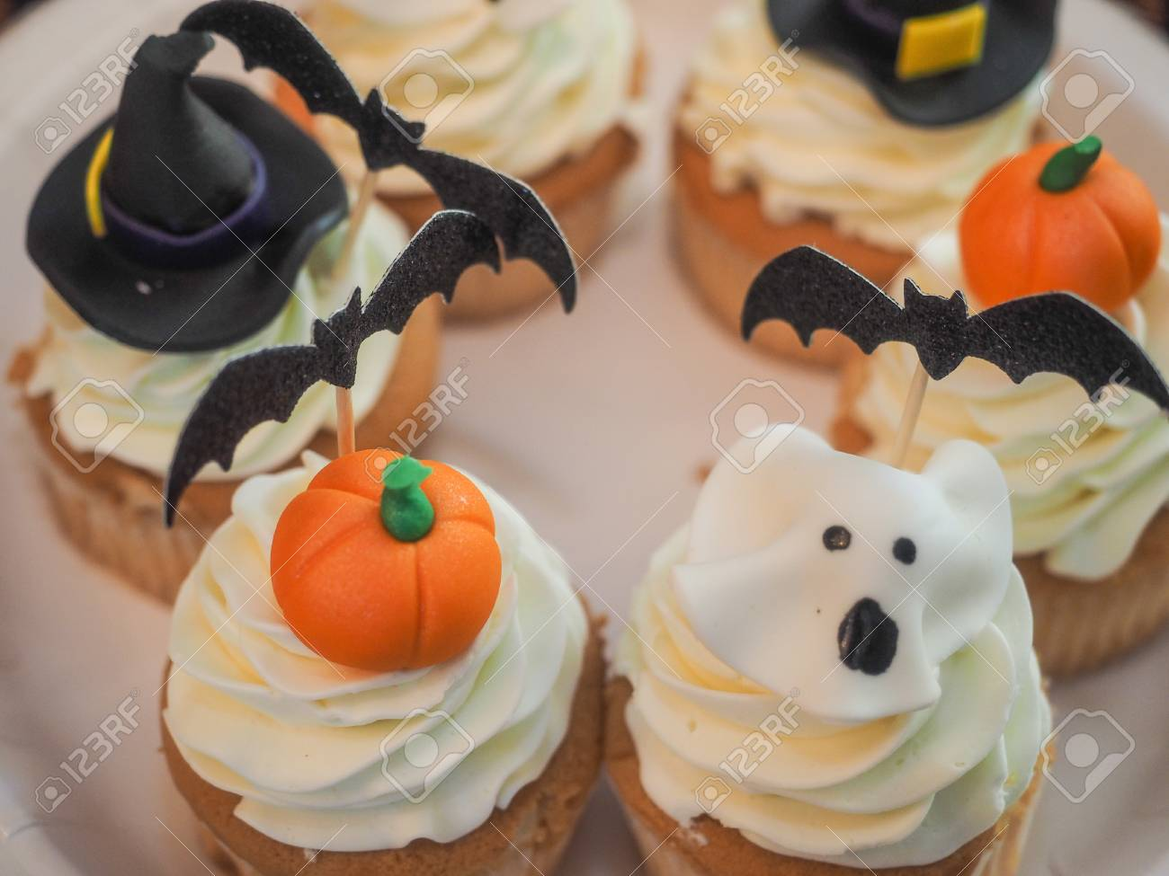 Spooky Halloween Cupcakes With White Cream And Decorations On