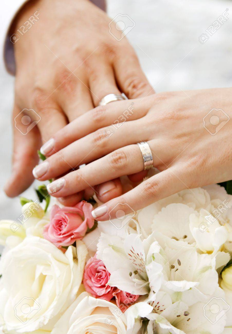 Hands and rings on wedding bouquet Stock Photo - 7354329