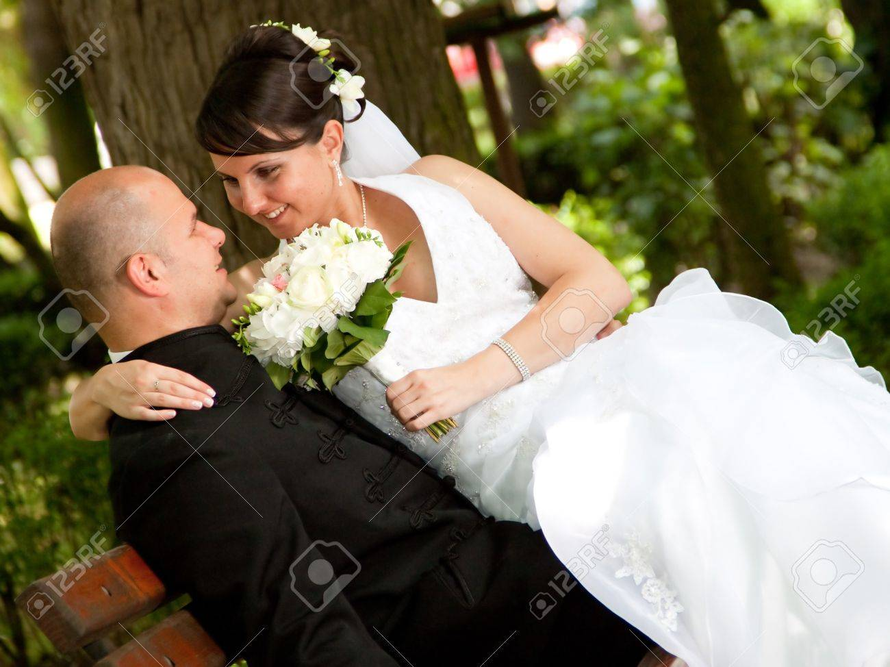 Bride and groom sitting on bench Stock Photo - 7348444
