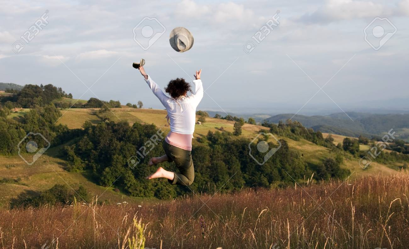 woman jumping on field and throwing her hat Stock Photo - 7592240