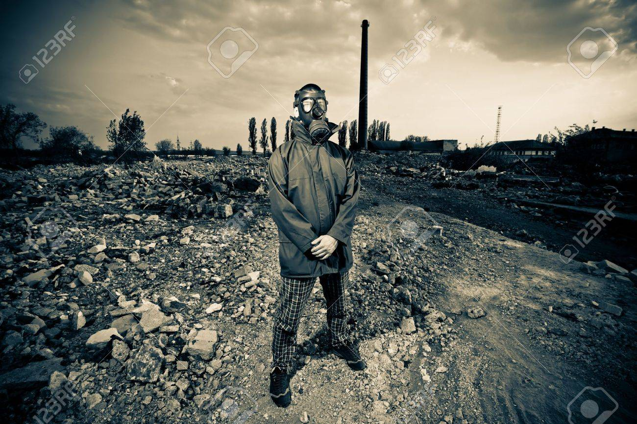 Bizarre portrait of man in gas mask on smoky industrial background with pipes after nuclear disaster Stock Photo - 9642119
