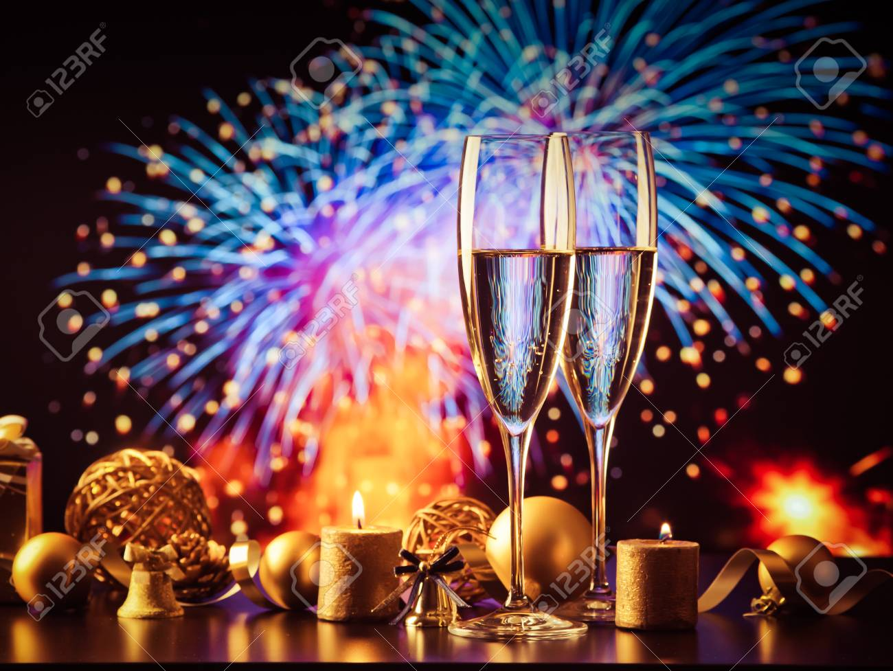 two champagne glasses against holiday lights and fireworks - new year celebration - 89395043