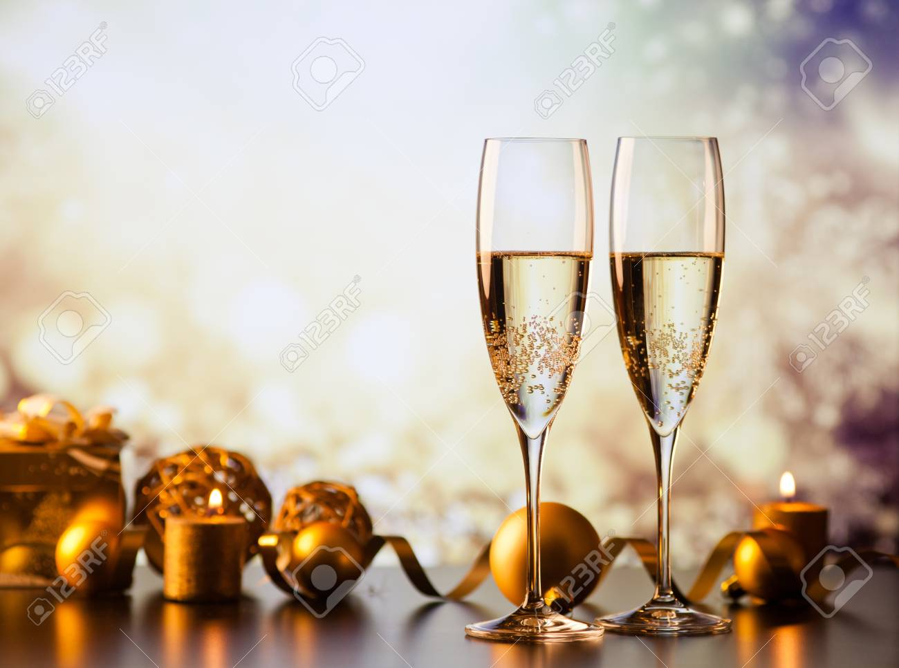 two champagne glasses against holiday lights and fireworks - new year celebration - 89411156