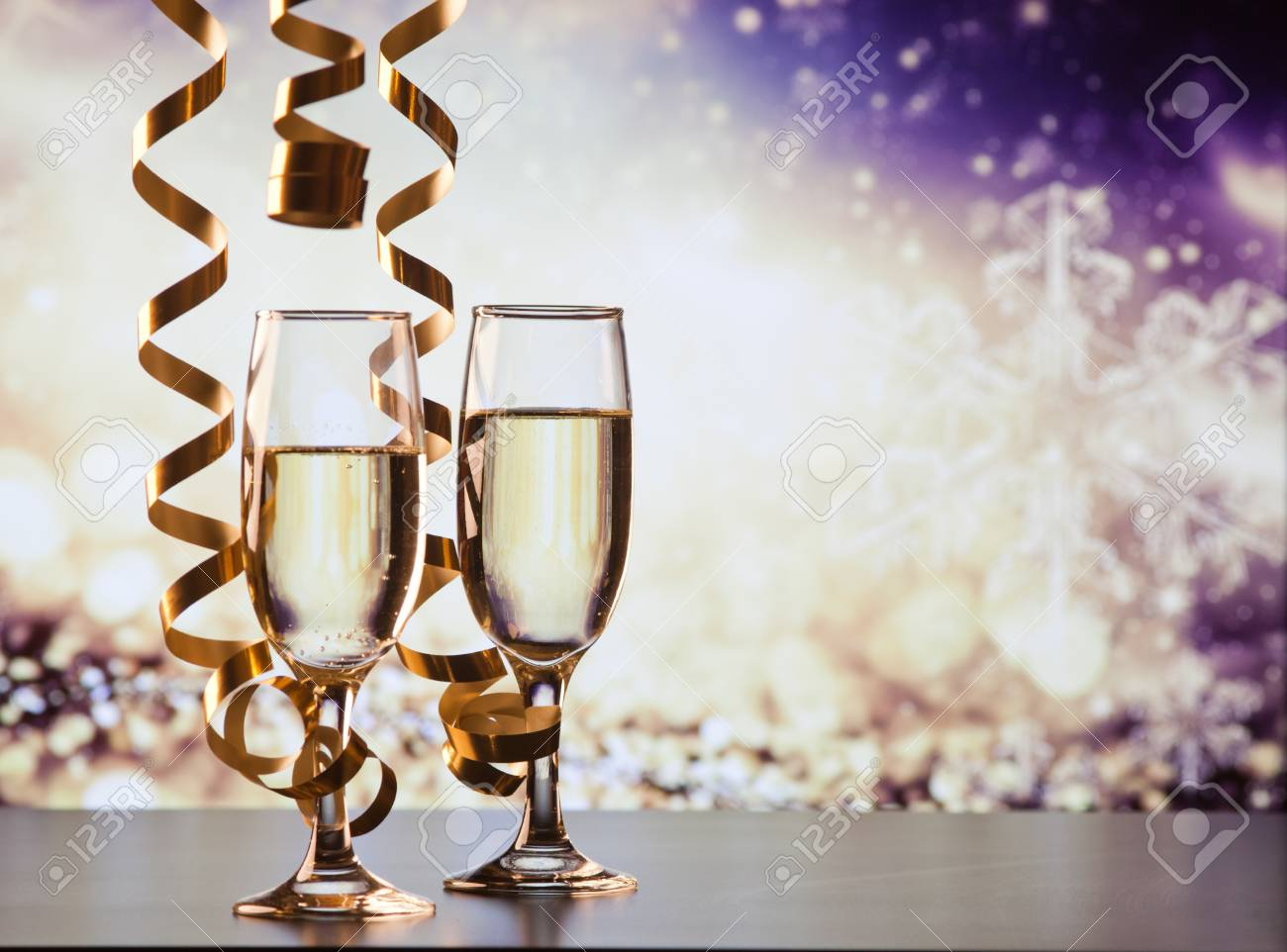 two champagne glasses with ribbons against holiday lights and fireworks - New Year celebrations - 89395740