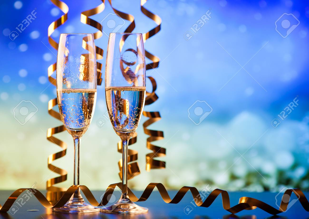 two champagne glasses with ribbons against holiday lights and fireworks - New Year celebrations - 89396040