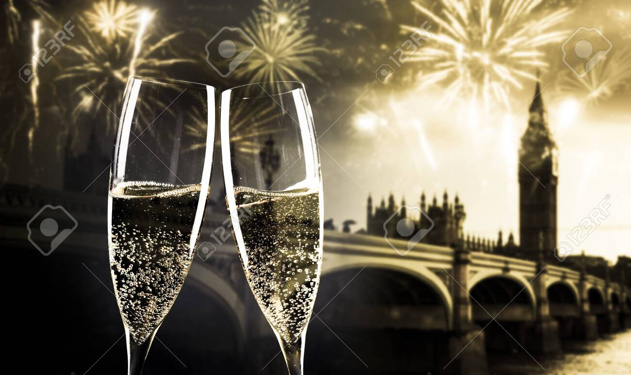 celebrating new year's eve in the city - toasting with champagne glasses in front of Big Ben - 135574643
