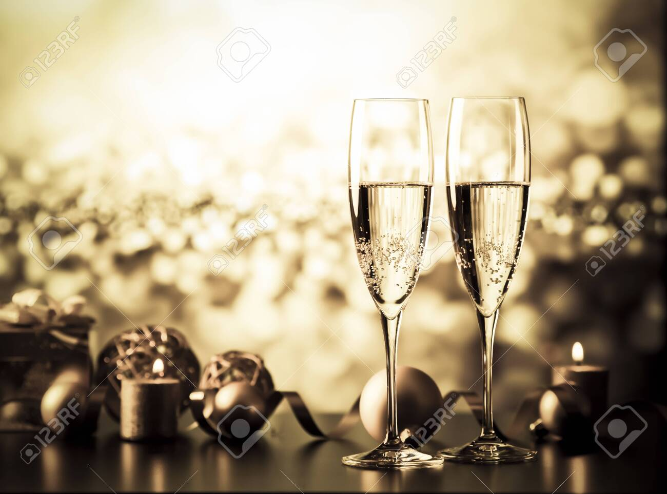 two champagne glasses against holiday lights and fireworks - new year celebration - 135574716