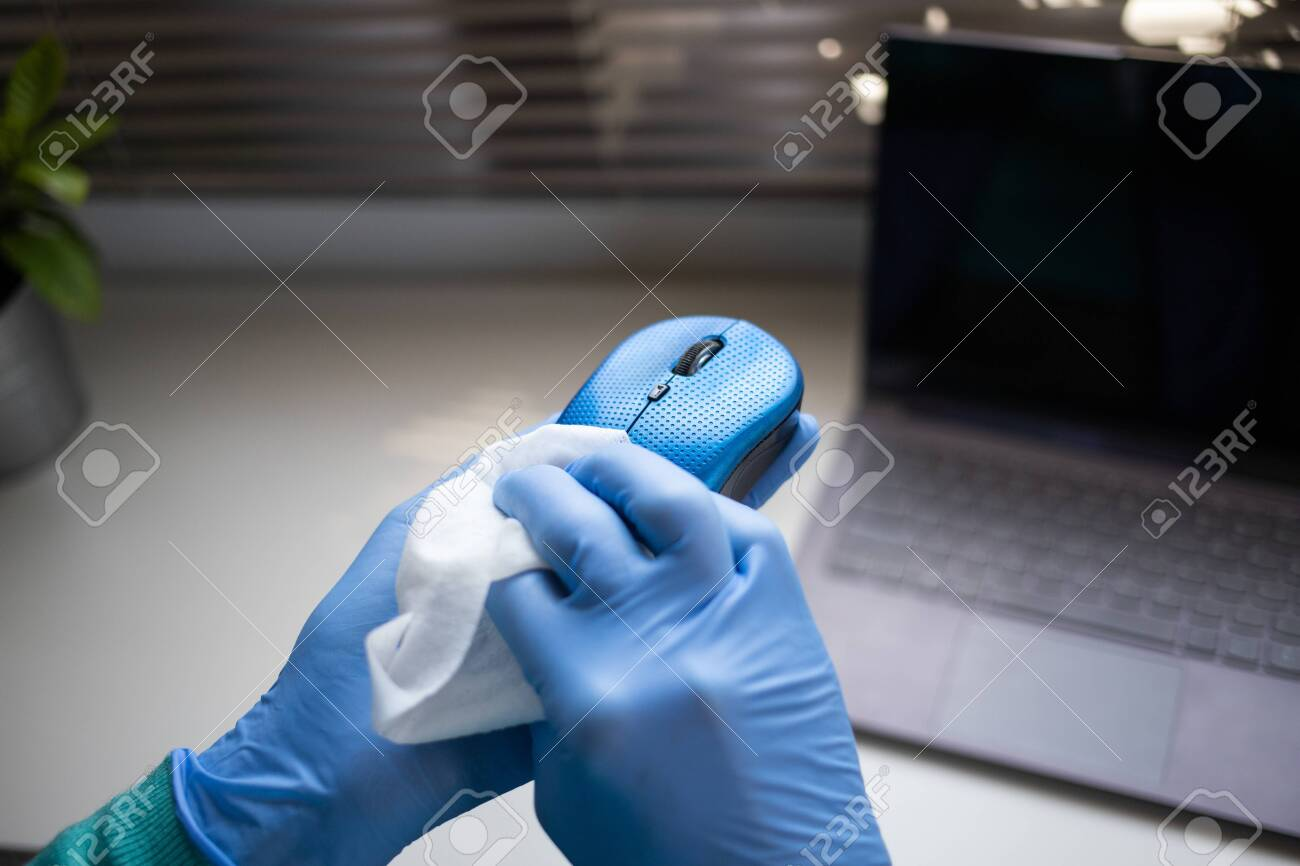 Office sanitizing wipe wiping mouse and mousepad with disinfecting wipes. Coronavirus COVID-19 sanitize cleaning disinfection of work desk. - 144848009