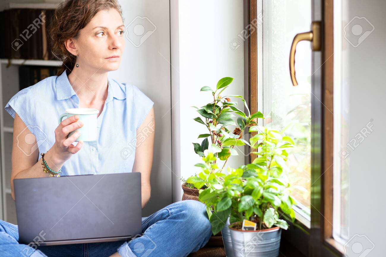 pensive woman working from home looking out on window thinking about future, relationship, career - 146878800