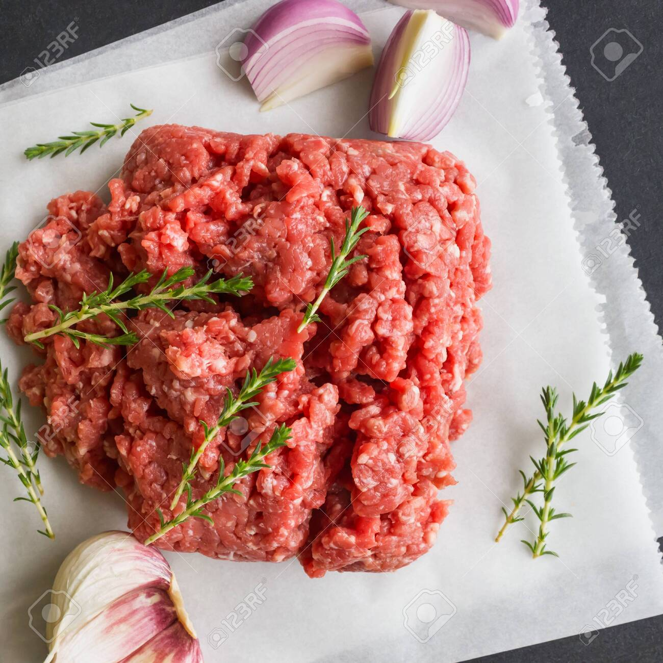 Raw minced meat with thyme and spices for cooking cutlets, hamburgers,