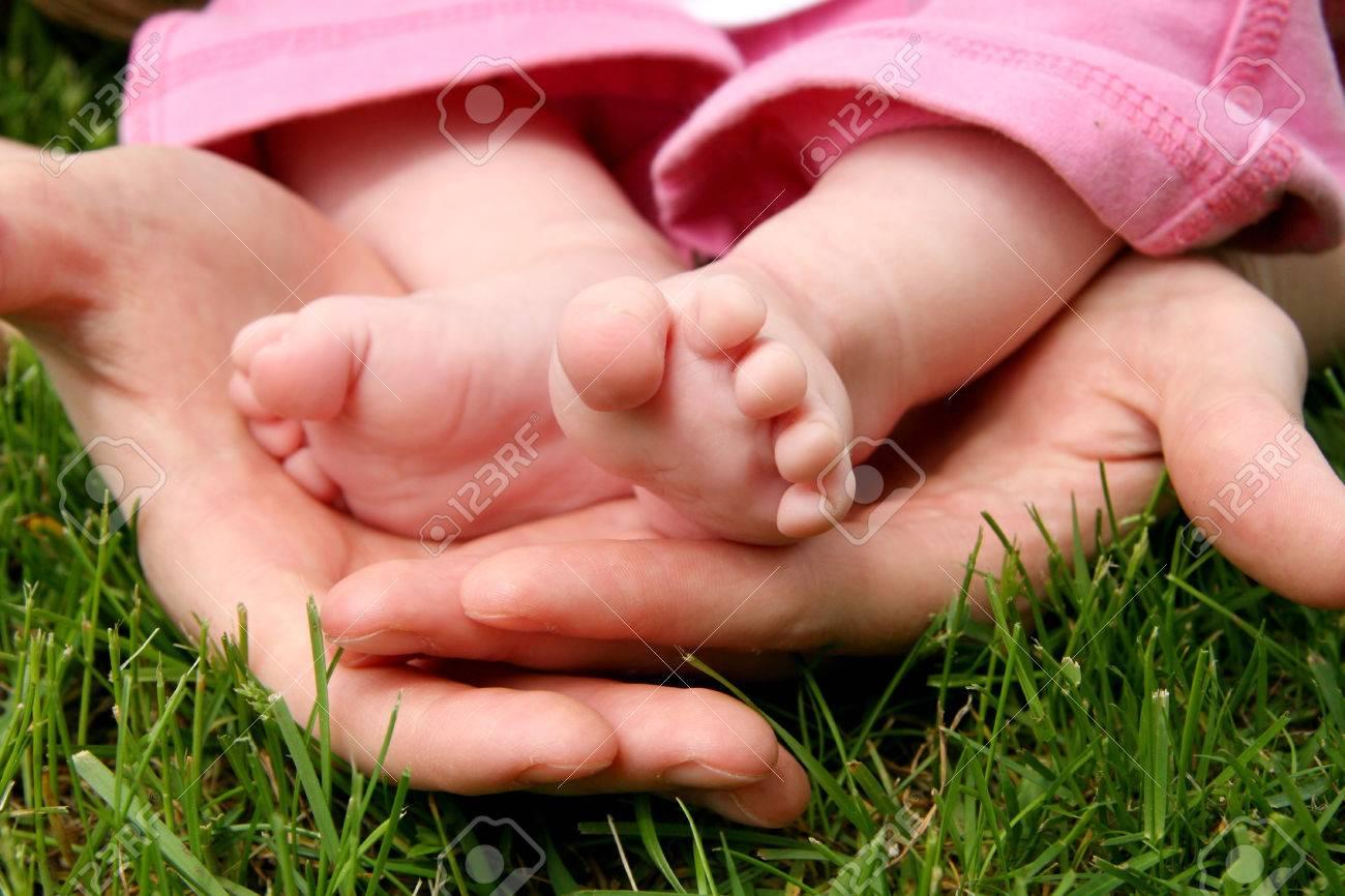 mother's hands cradling her infant daughter's feet - 1484136
