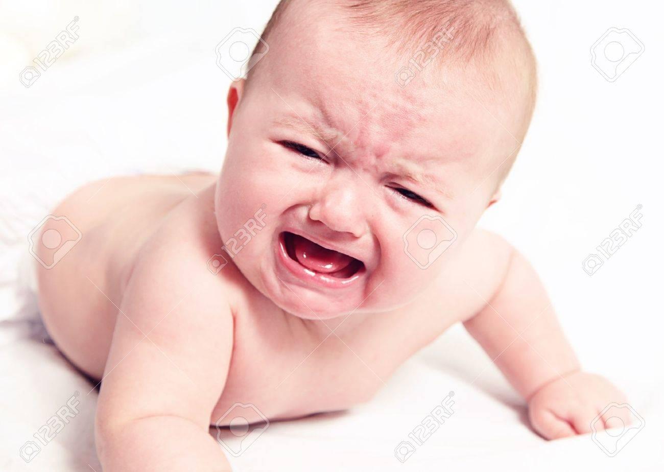 Little baby girl crying on white blanket - 12010415