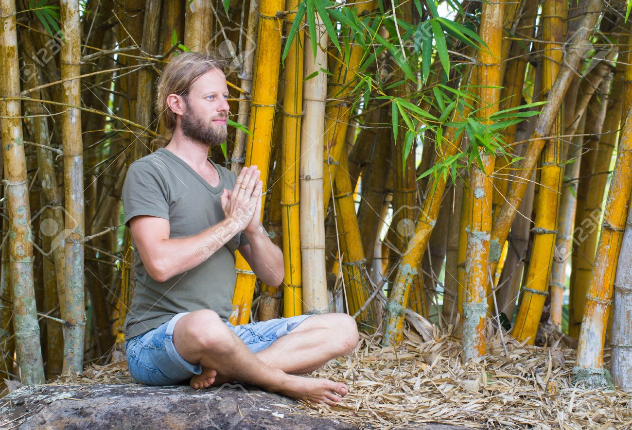 Attractive Man Doing Yoga In An Outdoor Bamboo Garden Hands