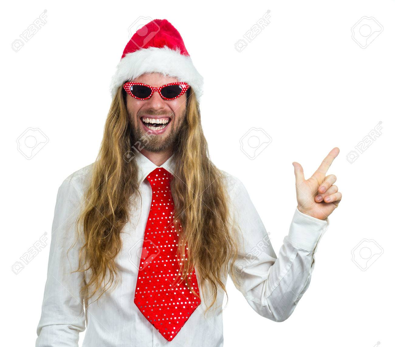 Silly happy hippie in a Santa hat and retro glasses pointing at copy-space. cdfcbace5ad