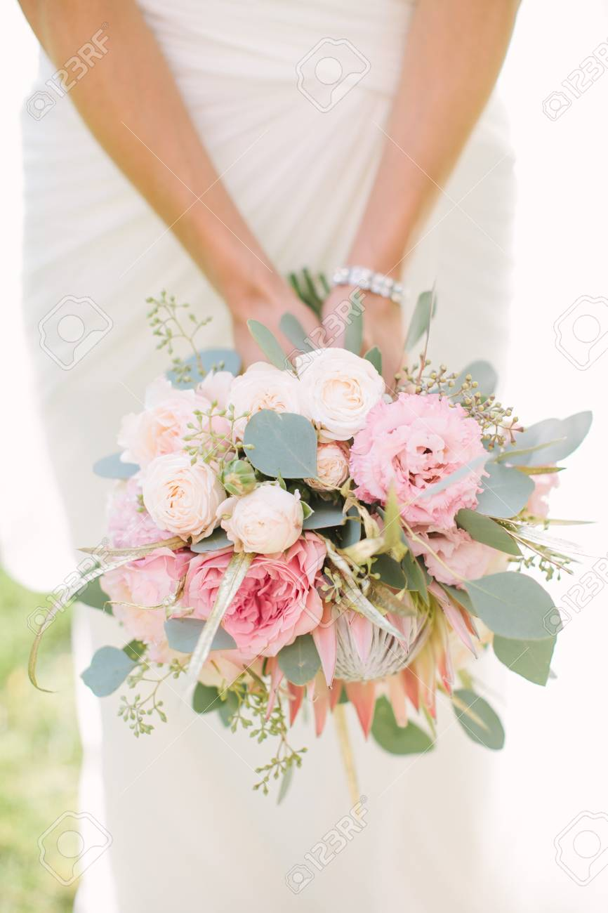 Woman In A White Wedding Dress Holding A Pink Flowers Bouquet
