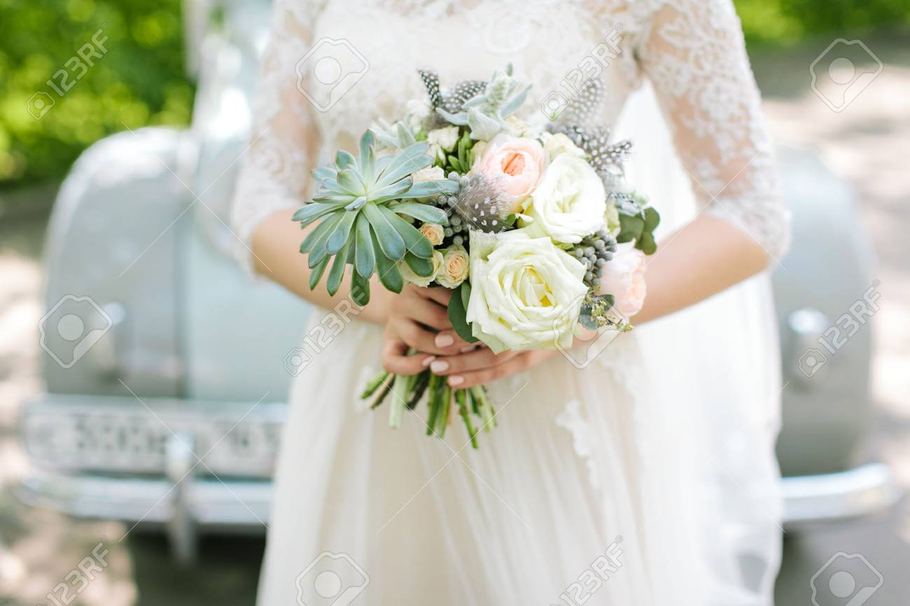 Beautiful Woman In A White Wedding Dress Holding A Flowers Bouquet ...