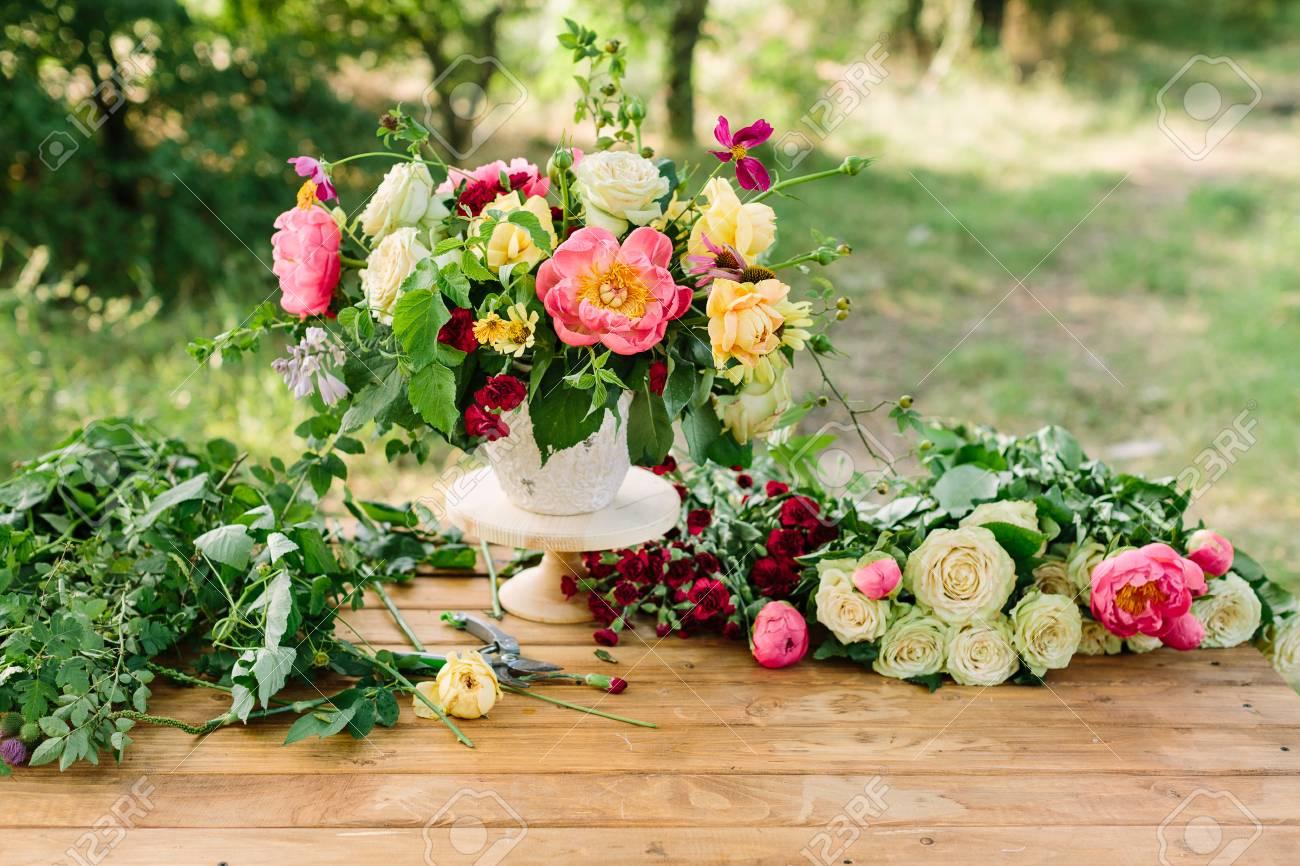 Ramo Día De Fiesta De Flores Regalo Y Concepto De Arreglo Floral Componer Un Maravilloso Ramo En Jarrón Blanco Sobre Mesa De Madera En El Jardín