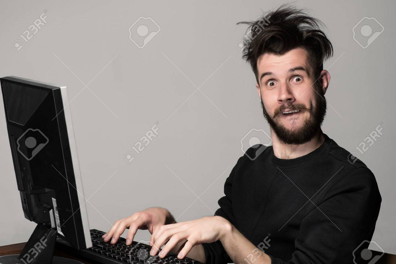 Funny and crazy man using a computer on gray background - 40507004