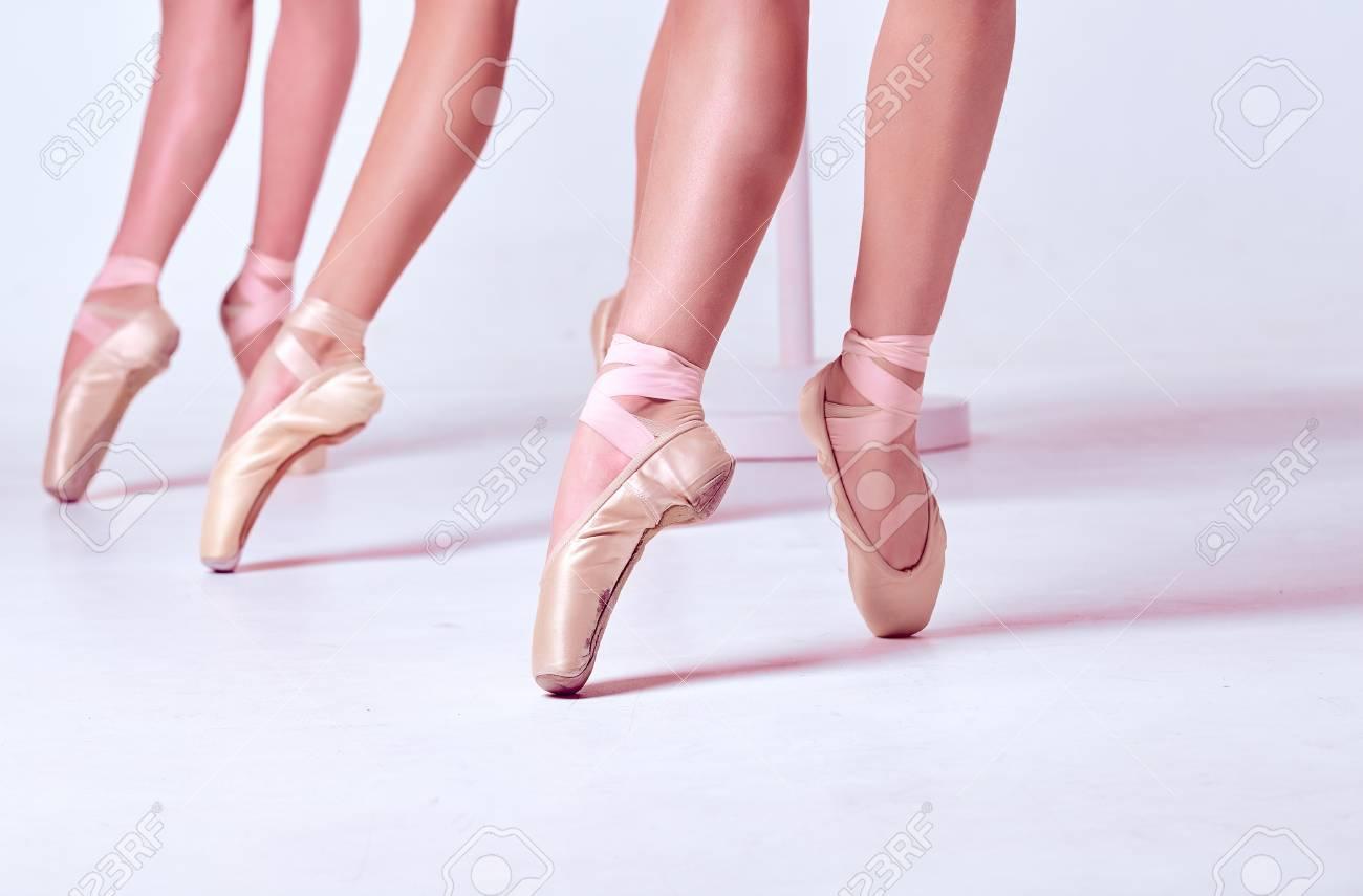 b455ab5934de9 Foto de archivo - Los pies en primer plano de unos tres bailarinas jóvenes  en zapatillas de punta contra el fondo del piso blanco