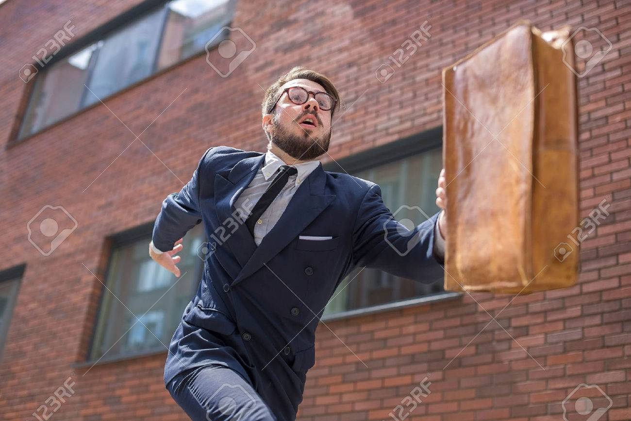 Young businessman with a briefcase and glasses running in a city street on a background of red brick wall. concept of rapid career - 43989911