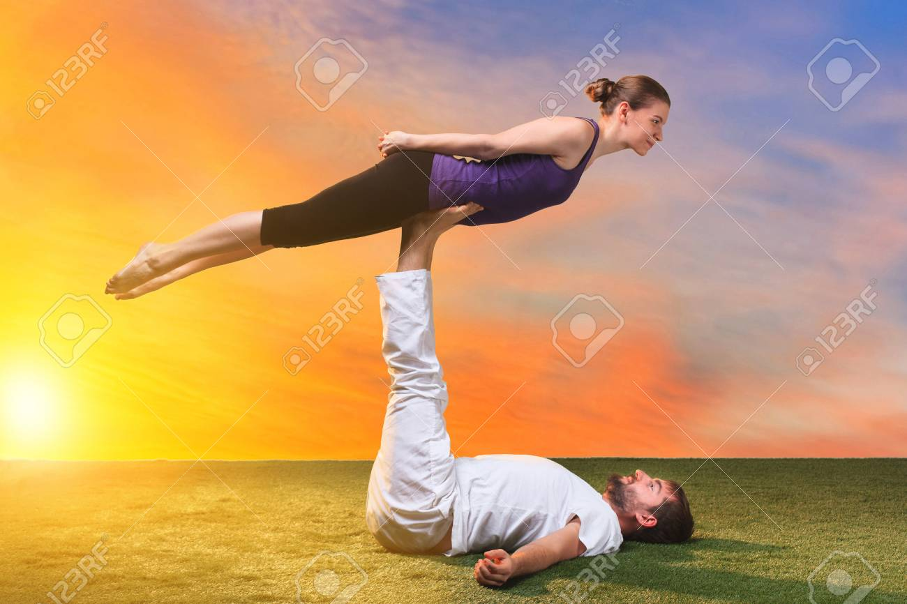 the two people doing yoga exercises against sunset sky stock photo