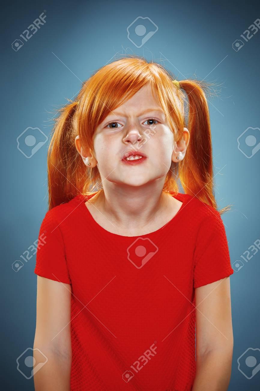 e2c6e8af1524b8 Het mooie portret van ontevreden en ontevreden meisje in een rode jurk op  blauw Stockfoto -