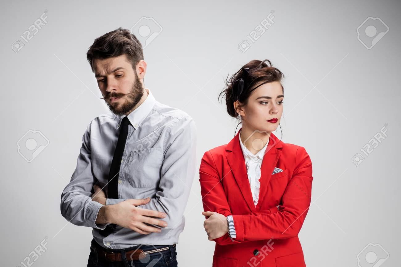 The funny sad business man and woman conflicting on a gray background