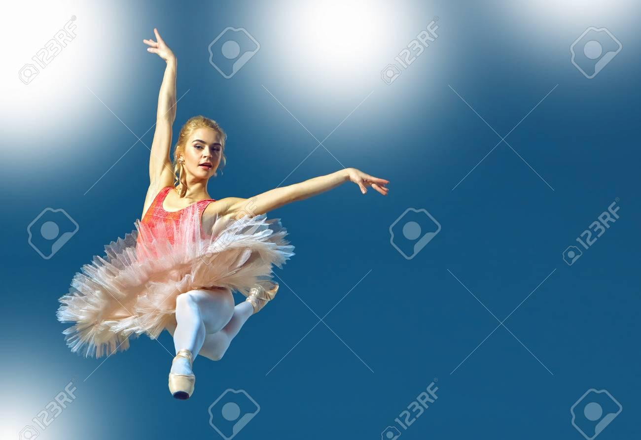 Hermoso bailarín de ballet femenino sobre un fondo gris. La bailarina está llevando los zapatos rosados ??del tutú y del pointe.