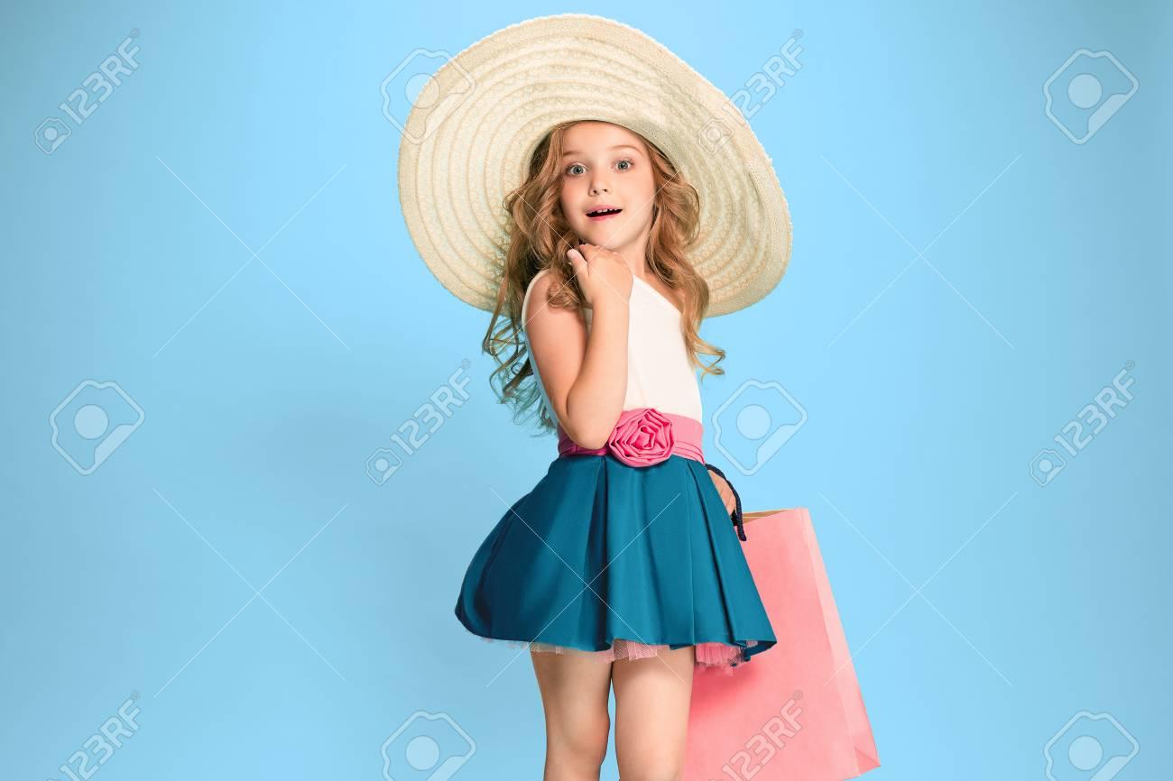 The cute little caucasian brunette girl in dress holding shopping bags - 83484327