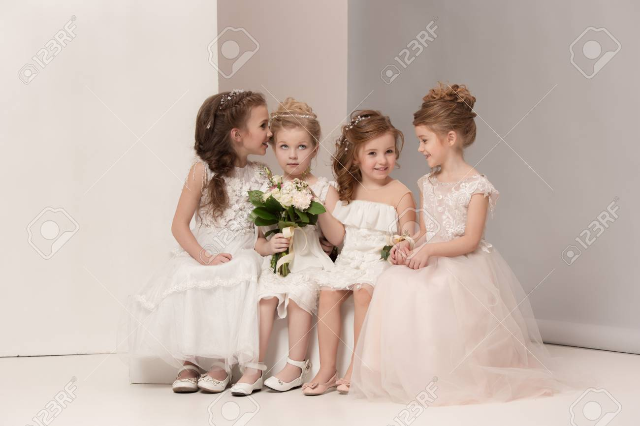 Little pretty girls with flowers dressed in wedding dresses - 97812378