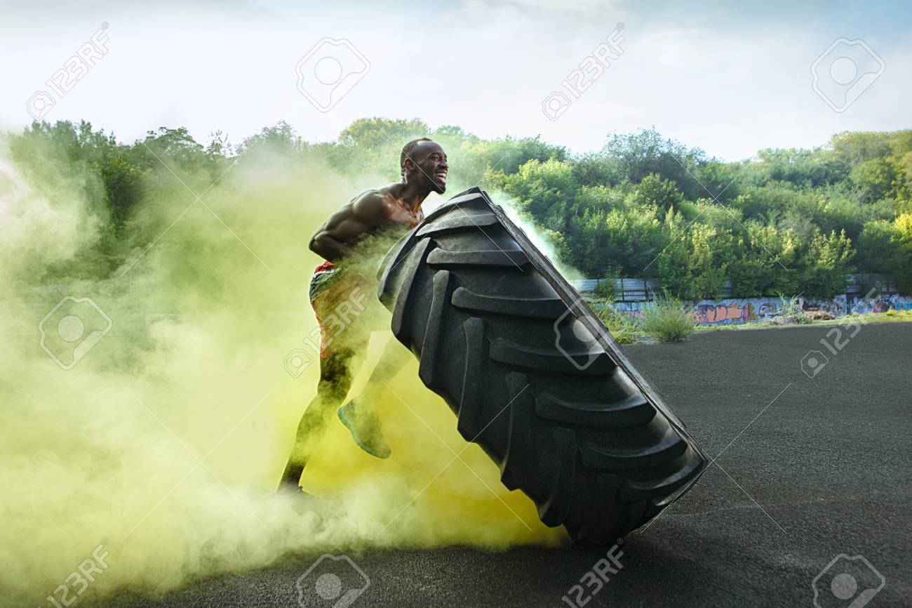 Handsome african american muscular man flipping burning big tire outdoor with smoke - 110013069
