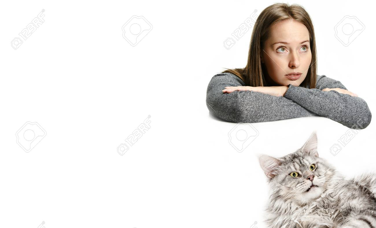 The funny sad woman and her cat looking serious over white background