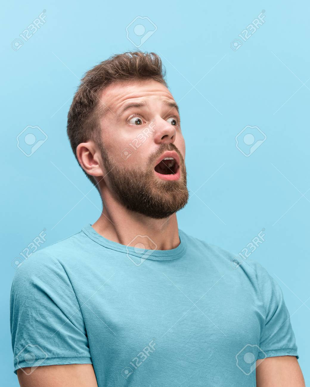 The surprised and astonished young man screaming with open mouth isolated on blue background. concept of shock face emotion - 112330193