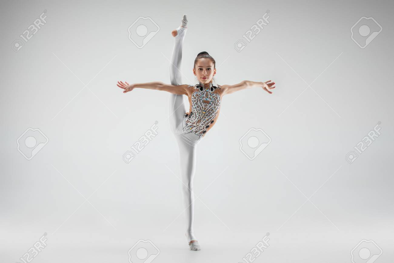 The teen female little girl doing gymnastics exercises isolated on a gray studio background. The gymnastic, stretch, fitness, lifestyle, training, sport concept - 112674469