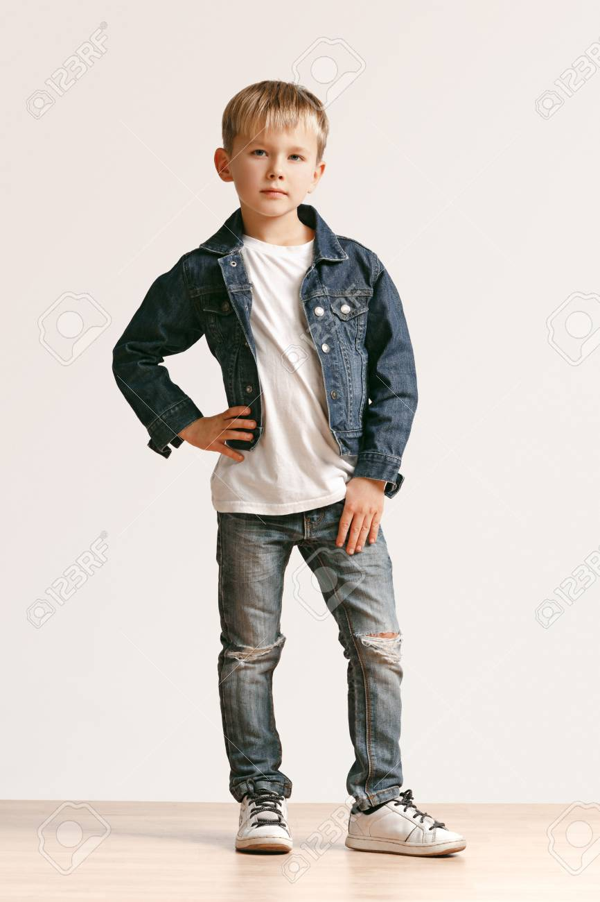 428116e67 Stock Photo - The portrait of cute little kid boy in stylish jeans clothes  looking at camera against white studio wall. Kids fashion concept