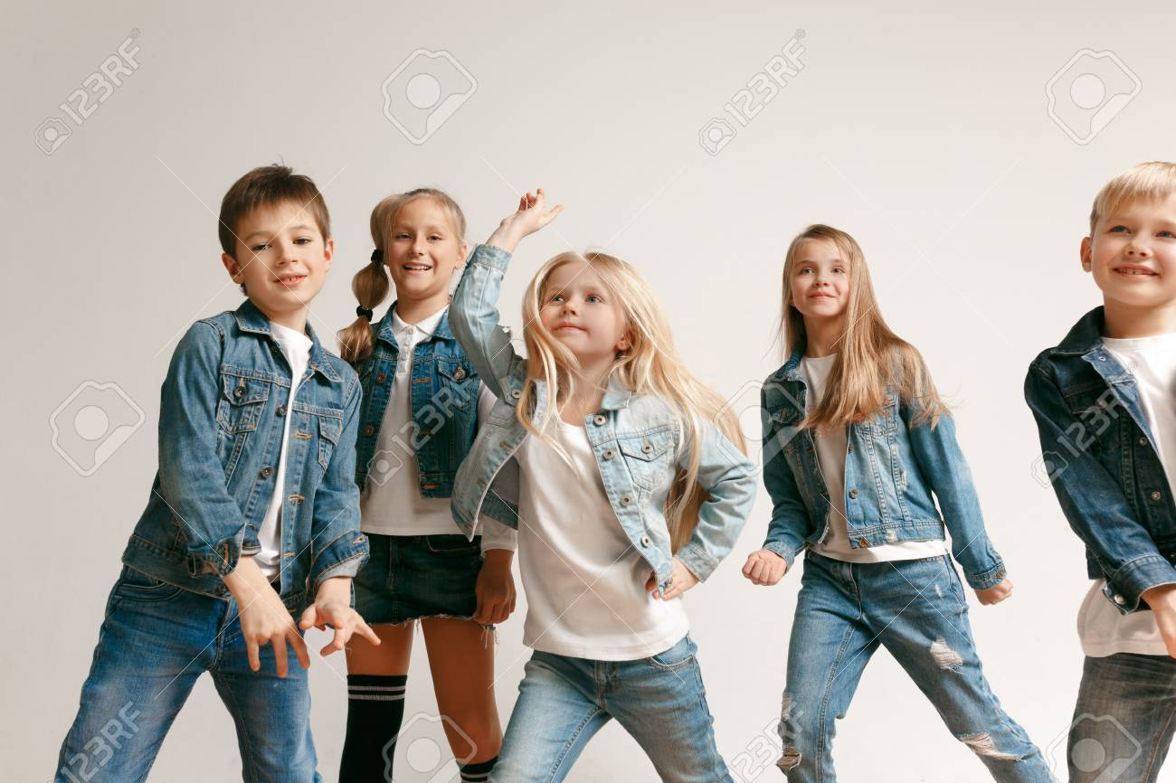 775c8bd5f Stock Photo - The portrait of cute little kids boy and girls in stylish  jeans clothes looking at camera against white studio wall.