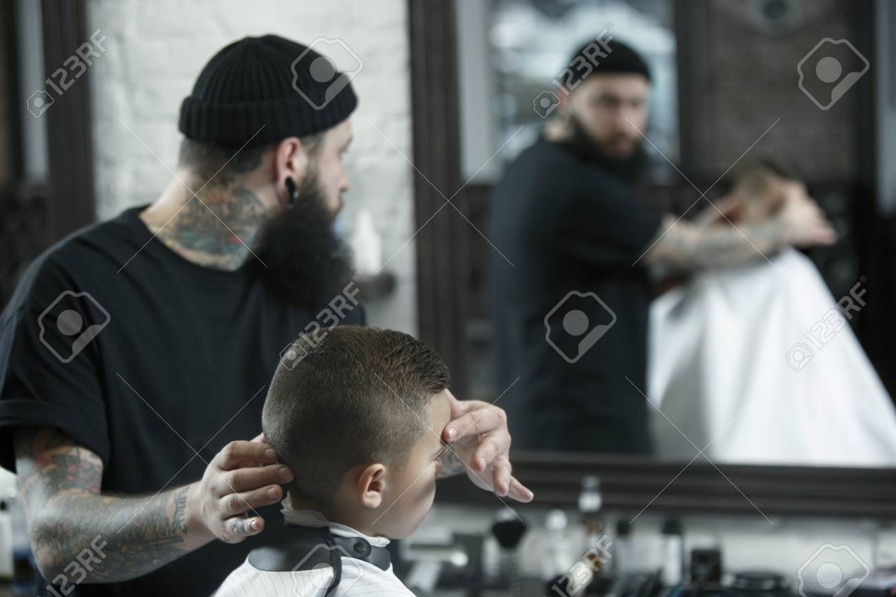 Children hairdresser cutting little boys hair. Contented cute..