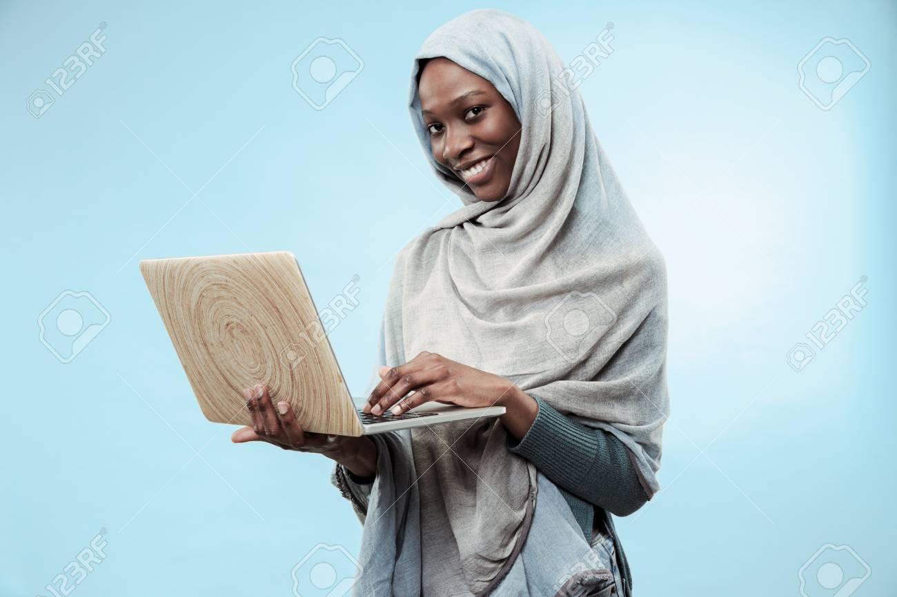Portrait Of Female University Student Working on laptop. The beautiful young black african muslim girl wearing gray hijab at blue studio. She standing with happy smile on her face. - 116260289