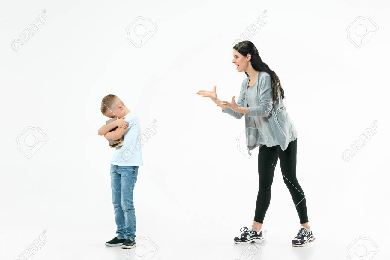 Angry mother scolding her son at home  Studio shot of emotional