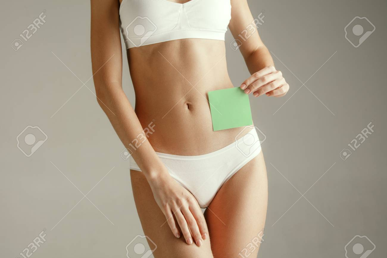 Woman health. Female model holding empty card near stomach. Young adult girl with paper for sign or symbol isolated on gray studio background. Cut out part of body. Medical problem and solution. - 119596704