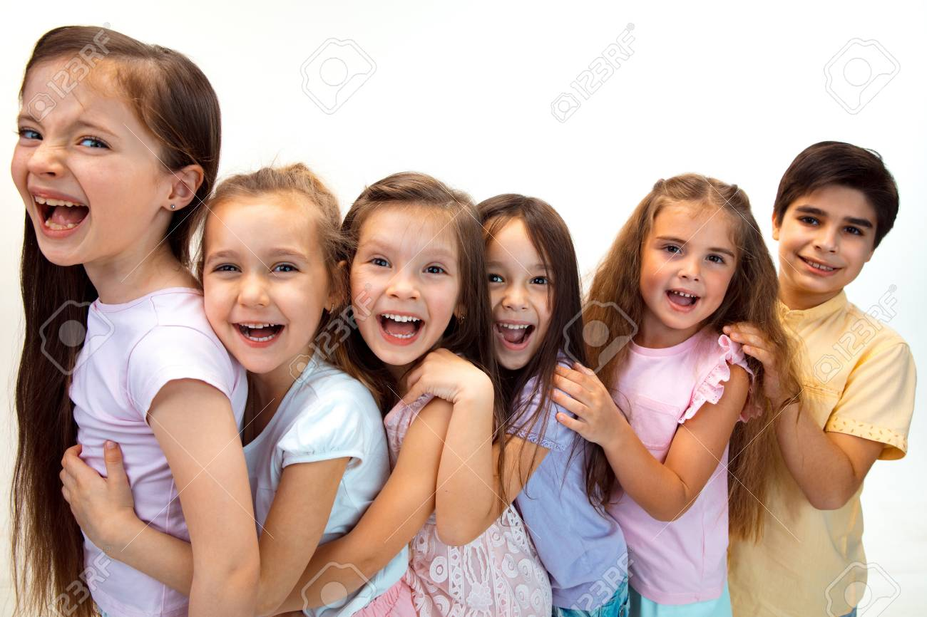 The portrait of happy cute little kids boy and girls in stylish casual clothes looking at camera against white studio wall. Kids fashion and human emotions concept - 120051052