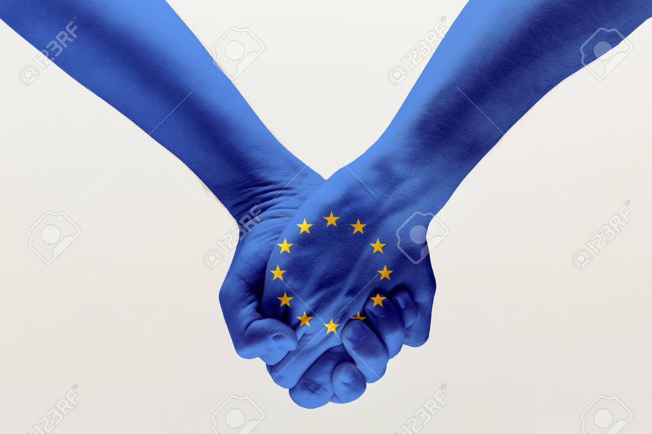 Peace and strong. Male hands holding colored in blue EU flag isolated on gray studio background. Concept of help, commonwealth, unity of European countries, political and economical relations. - 120651037