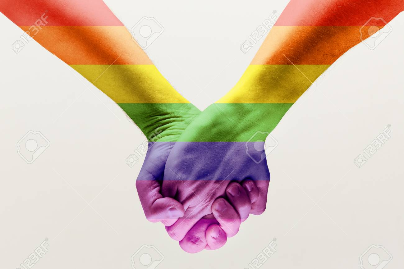 Right to choose your own way. loseup shot of a couple holding hands, patterned as the rainbow flag isolated on white studio background. Concept of LGBT, activism, community and freedom. - 120651044