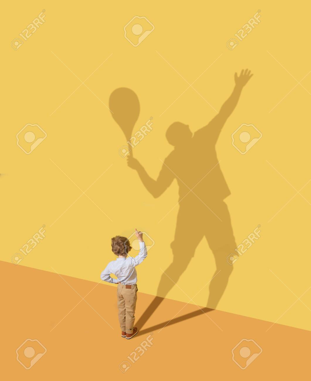 Getting best result in team. Childhood and dream concept. Conceptual image with child and shadow on the yellow studio wall. Little boy want to become tennis player and to build a sport career. - 121063406