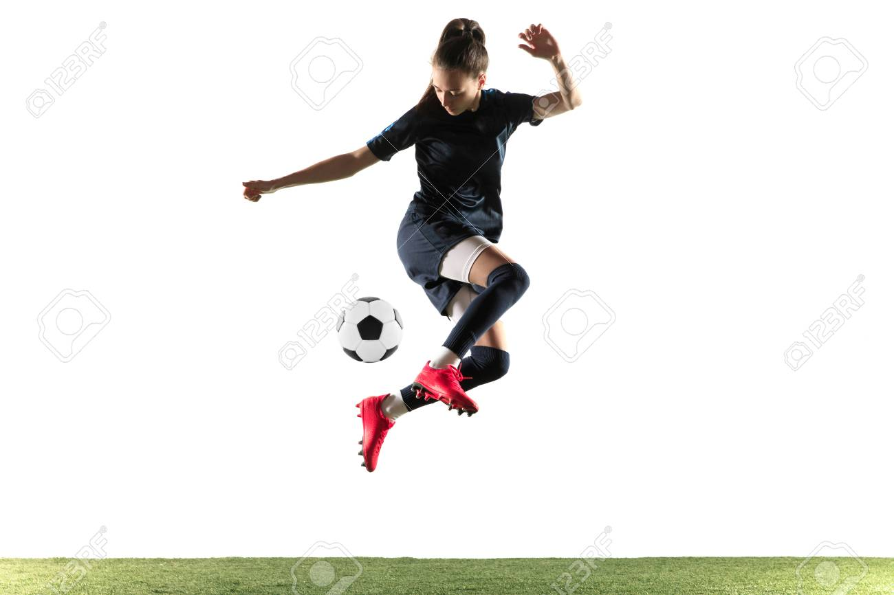 Young female soccer or football player with long hair in sportwear and boots kicking ball for the goal in jump isolated on white background. Concept of healthy lifestyle, professional sport, hobby. - 121278554