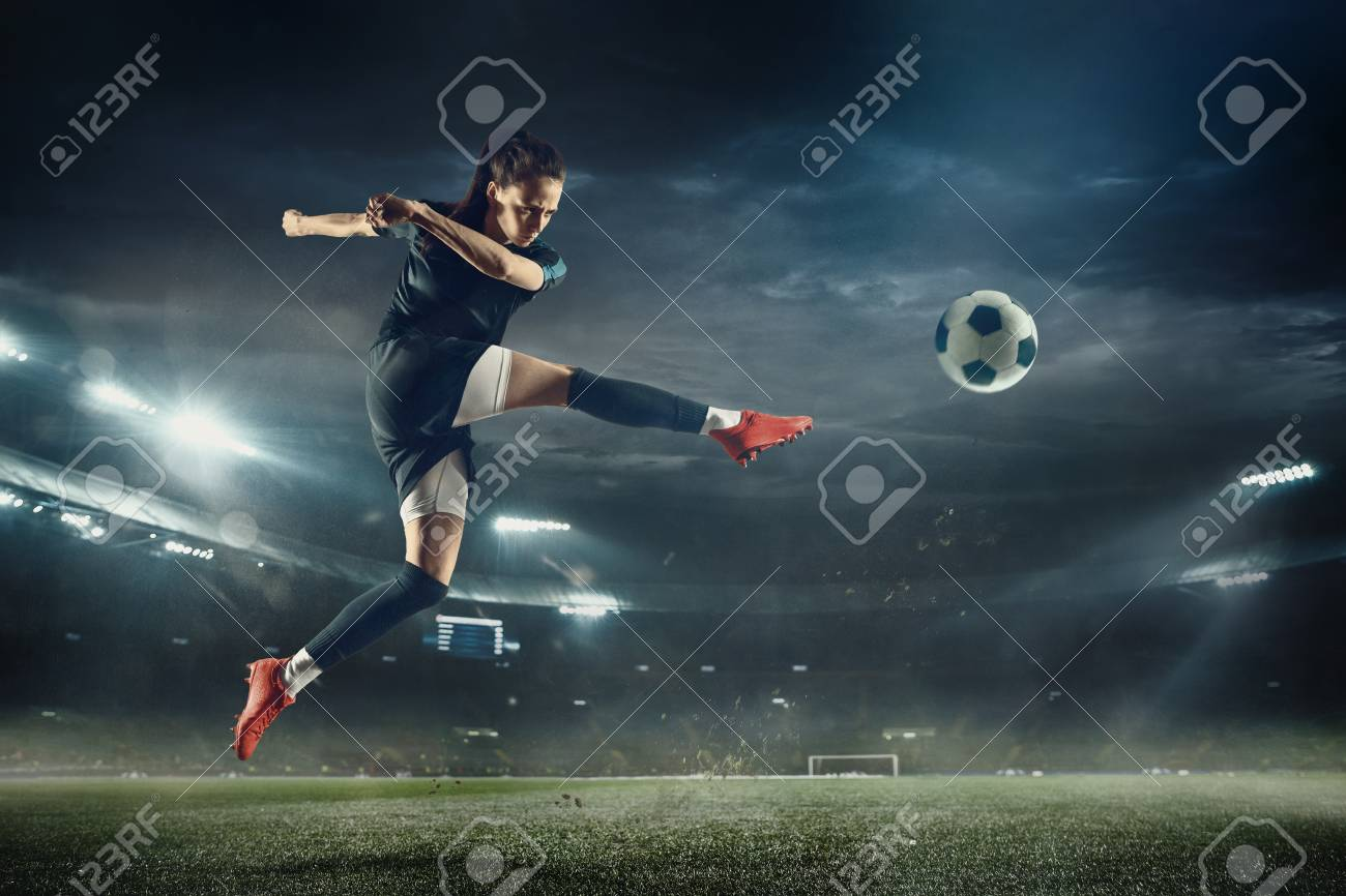 Young female soccer or football player with long hair in sportwear and boots kicking ball for the goal in jump at the stadium. Concept of healthy lifestyle, professional sport, hobby, motion, movement. - 122981665