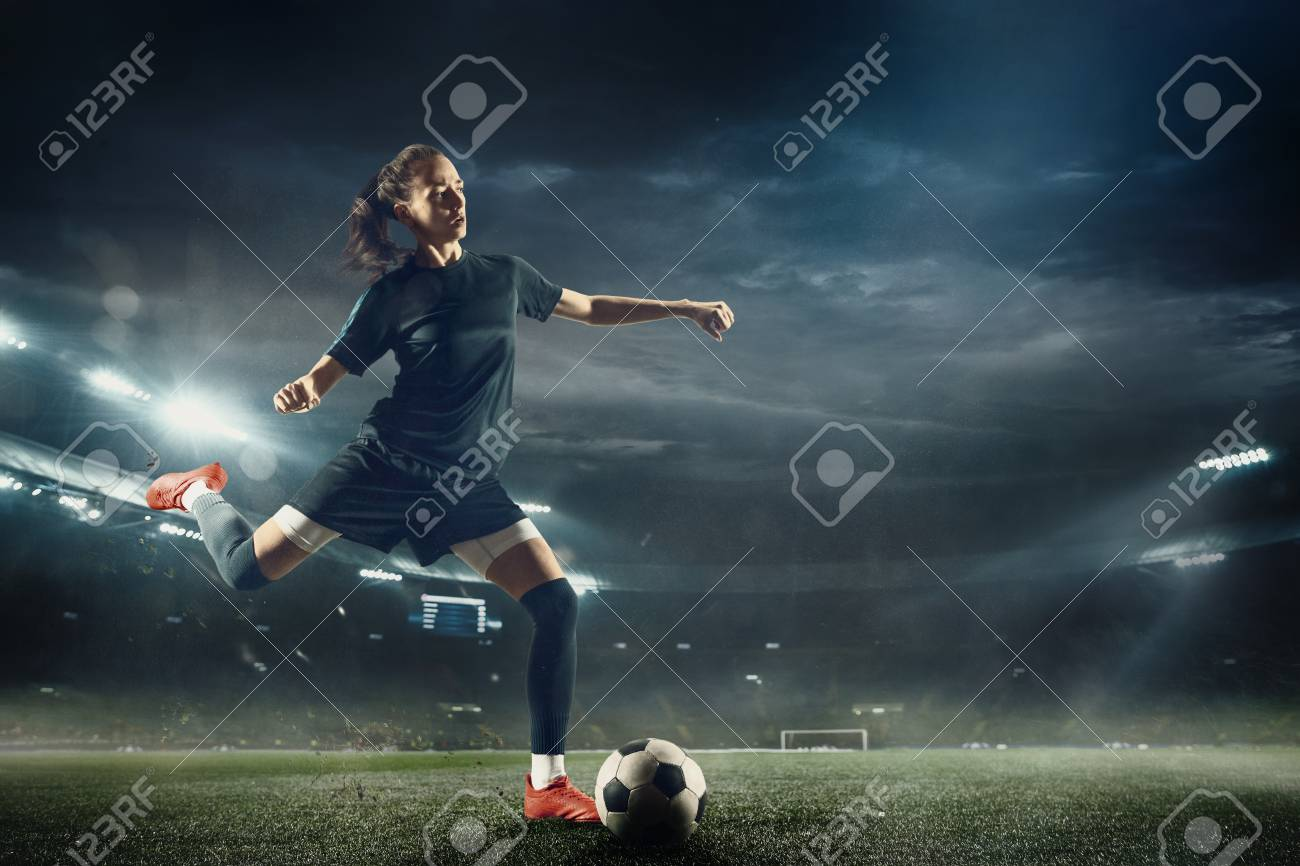 Young female soccer or football player with long hair in sportwear and boots kicking ball for the goal in jump at the stadium. Concept of healthy lifestyle, professional sport, hobby, motion, movement. - 122981666