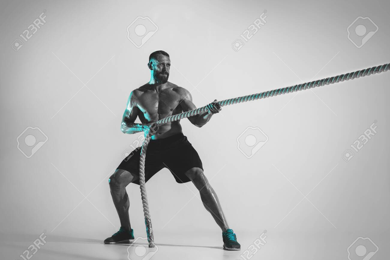 Comparison of forces. Young caucasian bodybuilder training over studio background in neon light. Muscular male model with the rope. Concept of sport, bodybuilding, healthy lifestyle, motion and action. - 124596081