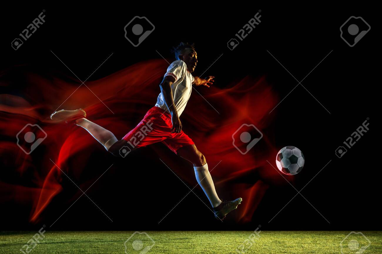 Young african-american male football or soccer player in sportwear and boots kicking ball for the goal in mixed light on dark background. Concept of healthy lifestyle, professional sport, hobby. - 124598474